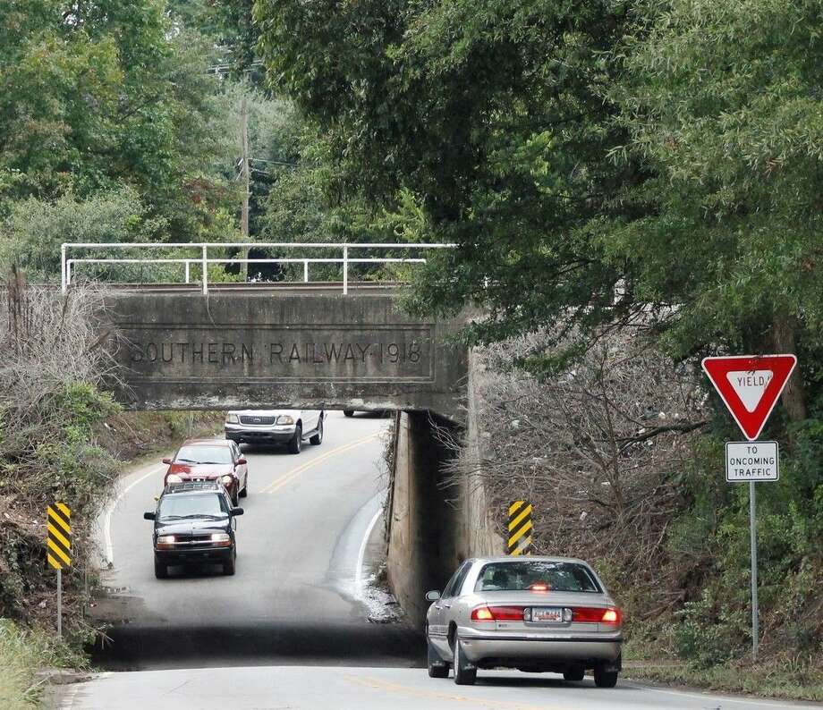 Cars head toward the railroad underpass in Spartanburg, S.C., where 56-year-old Sylvia Arteaga was killed on Thursday, Oct. 1, 2015, when flood waters inundated her car as she was driving home from work. The underpass is not wide enough to accommodate two cars, so motorists must alternate going under it. (AP Photo/Skip Foreman)