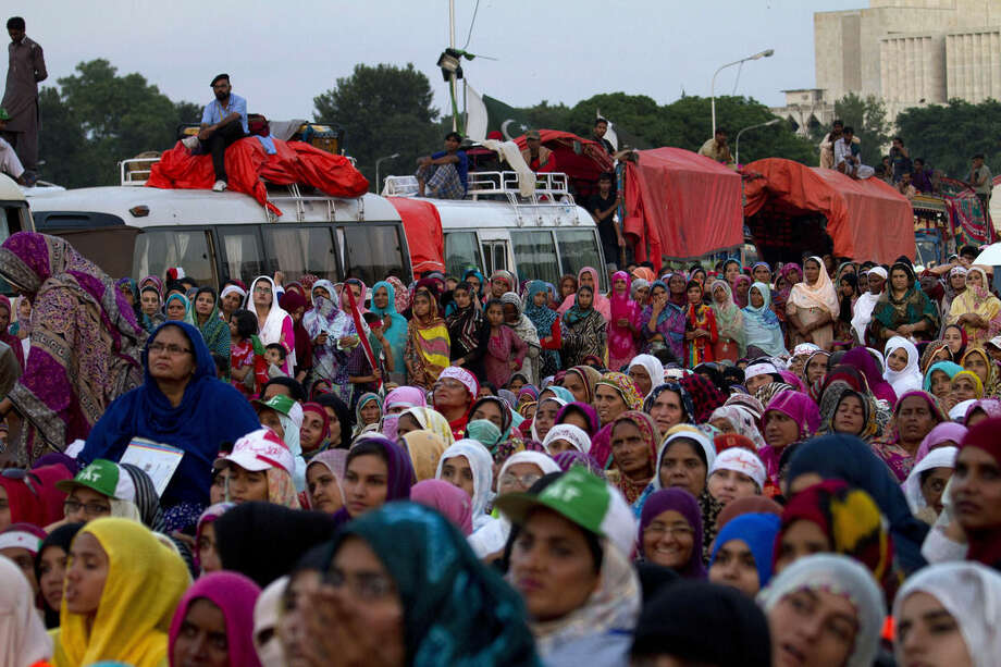 Women supporters of Pakistan's fiery Muslim cleric Tahir-ul-Qadri listen to his speak during a protest near the parliament building in Islamabad, Pakistan, Saturday, Aug 30, 2014. Thousands of supporters of cricketer-turned-politician Imran Khan and ul-Qadri have led parallel anti-government protests to pressure Prime Minister Nawaz Sharif to resign over alleged election fraud. (AP Photo/Anjum Naveed)