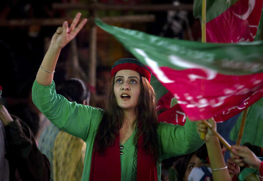 A woman supporter of Pakistan's cricketer-turned-politician Imran Khan flashes victory signs during a protest near the parliament building in Islamabad, Pakistan, Saturday, Aug 30, 2014. Thousands of supporters of Khan and Muslim cleric Tahir-ul-Qadr have held parallel anti-government protests to pressure Prime Minister Nawaz Sharif to resign over alleged election fraud. (AP Photo/Anjum Naveed)