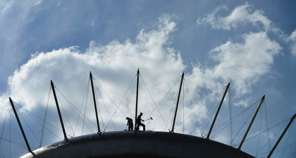 In this Sept. 15, 2015 photo, painters work on top of the water tank in Delano Park in Decatur, Ala. The U.S. government issues the September jobs report on Friday, Oct. 2, 2015. (Gary Cosby Jr./The Decatur Daily via AP)