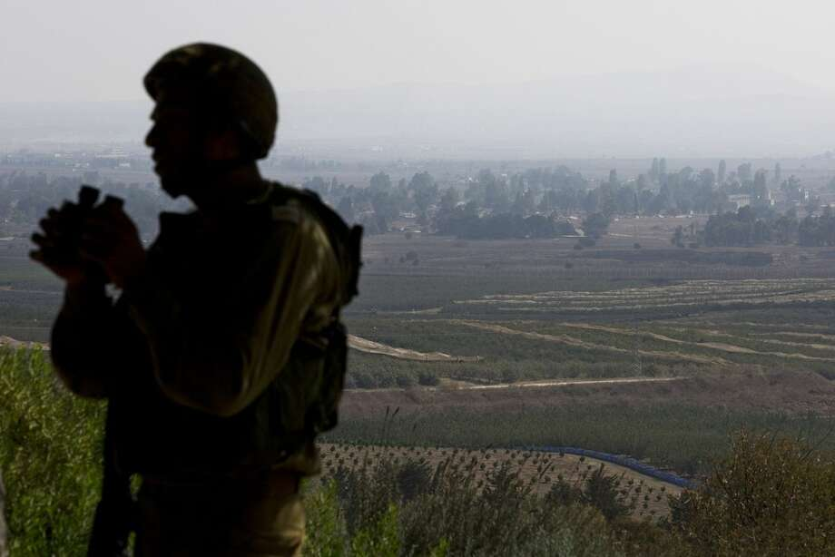 An Israeli soldier observes Syria's Quneitra province at an observation point on Mount Bental in the Israeli-controlled Golan Heights, overlooking the border with Syria, Monday, Sept. 1, 2014. (AP Photo/Sebastian Scheiner)