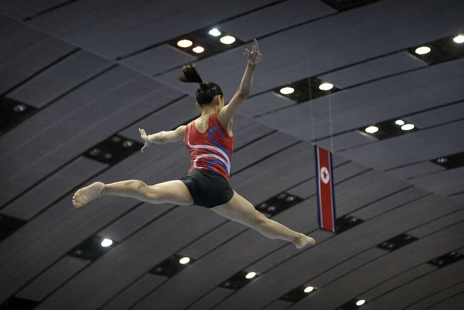 A gymnast practices her routine on the balance beam with the national flag of North Korea in the background on Tuesday, Sept. 2, 2014 in Pyongyang, North Korea. In just over a week, North Korea will send its top athletes to win gold for their leader in what could well be the biggest sporting event of their lives and a major propaganda campaign for their nation, the Asian Games in Incheon, South Korea.(AP Photo/Wong Maye-E)