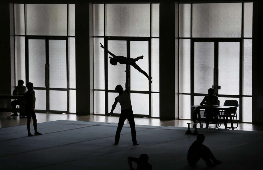Gymnasts are silhouetted as they practice their routine, Tuesday, Sept. 2, 2014 in Pyongyang, North Korea. In just over a week, North Korea will send its top athletes to win gold for their leader in what could well be the biggest sporting event of their lives and a major propaganda campaign for their nation, the Asian Games in Incheon, South Korea.(AP Photo/Wong Maye-E)