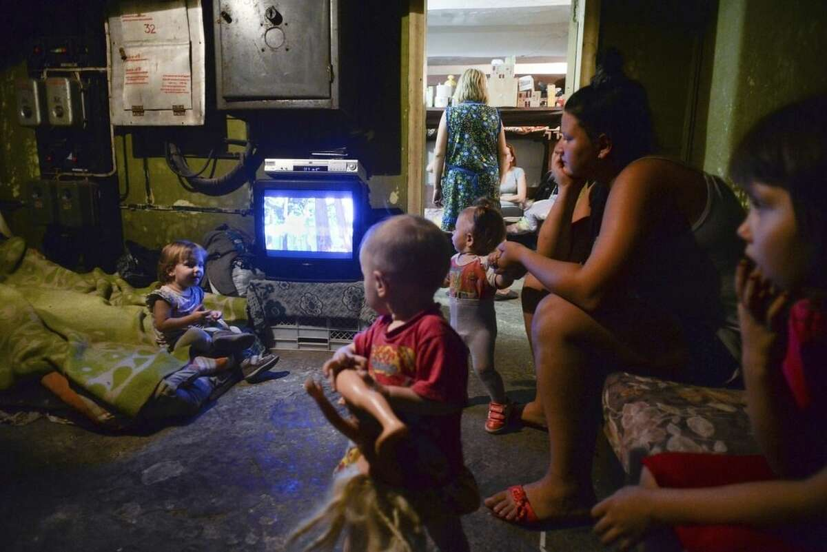 Families with children hide in the bomb shelter in Petrovskiy district in Donetsk, eastern Ukraine, Monday Sept. 1, 2014. The Petrovskiy district of Donetsk is currently a frontline and one of the districts which has suffered the most from the artillery fights between Ukrainian army and Pro-Pussian rebels. (AP Photo/Mstislav Chernov)