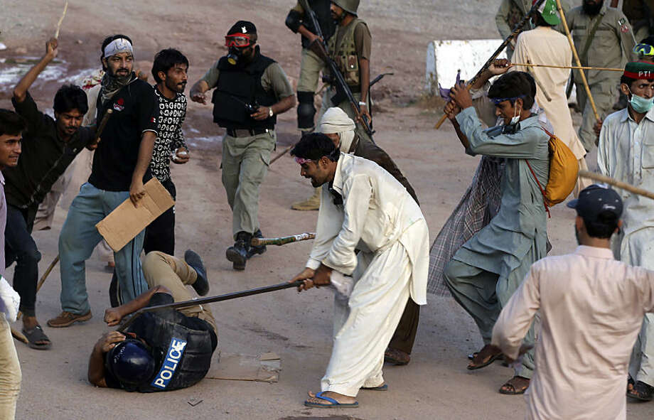 Pakistani protesters beat a police officer during a clash in Islamabad, Pakistan, Monday, Sept. 1, 2014. Anti-government protesters stormed Pakistan's state television building Monday, forcing the channel briefly off the air as they clashed with police and pushed closer to the prime minister's residence. The violence comes as part of the mass demonstrations led by Muslim cleric Tahir-ul-Qadri and opposition politician Imran Khan that demand Prime Minister Nawaz Sharif resign. (AP Photo/Anjum Naveed)