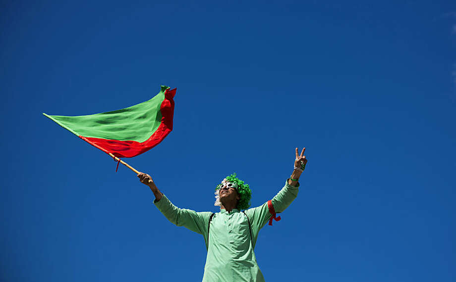 A supporter of Pakistan Tehrik-e-Insaf, headed by former cricket celebrity Imran Khan, waves a party flag outside a state TV headquarters in Islamabad, Pakistan, Monday, Sept. 1, 2014. Anti-government protesters and Pakistani police have clashed once again as the demonstrators pushed into a sprawling government complex in the country's capital in an effort to try to reach the prime minister's official residence. (AP Photo/B.K. Bangash)
