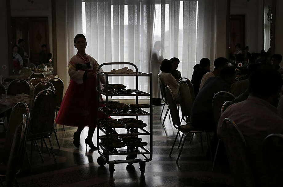 A North Korean waitress is silhouetted as she pushes a trolley of noodles at the Ongyugwan dining hall of a popular noodle restaurant, Monday, Sept. 1, 2014 in Pyongyang, North Korea. The restaurant, built in 1960 at the instructions of the late leader Kim Il Sung, claims to serve 10,000 lunches a day. (AP Photo/Wong Maye-E)