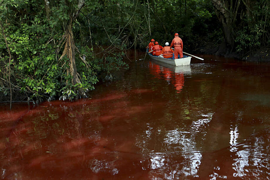 Workers from a company outsourced by Mexico's state-owned oil company Pemex navigate the contaminated Hondo River as they work to remove premium gasoline from the water, caused by a pipeline spill near the town of Tierra Blanca, Mexico, Sunday, Aug. 31, 2014. According to PEMEX, the Aug. 27 spill was caused by an illegal tap in the pipeline by criminals trying to steal fuel. (AP Photo/Felix Marquez)