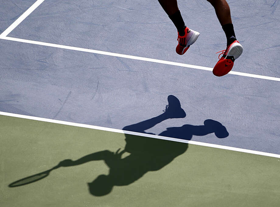 The shadow of Jo-Wilfried Tsonga, of France, is seen as he returns a shot against Andy Murray, of the United Kingdom, during the fourth round of the 2014 U.S. Open tennis tournament, Monday, Sept. 1, 2014, in New York. (AP Photo/Seth Wenig)
