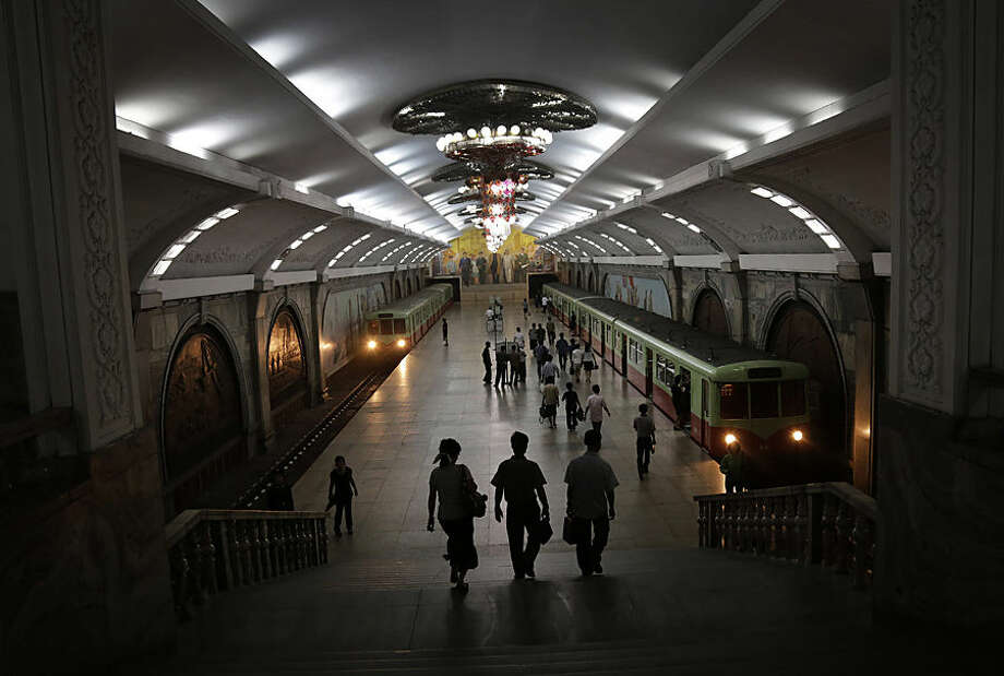 North Koreans walk in an underground subway station as two trains arrive at the platform, Monday, Sept. 1, 2014 in Pyongyang, North Korea. Foreign visitors are usually only allowed to take one to two stops, on Pyongyang's north-south Chollima subway line. (AP Photo/Wong Maye-E)