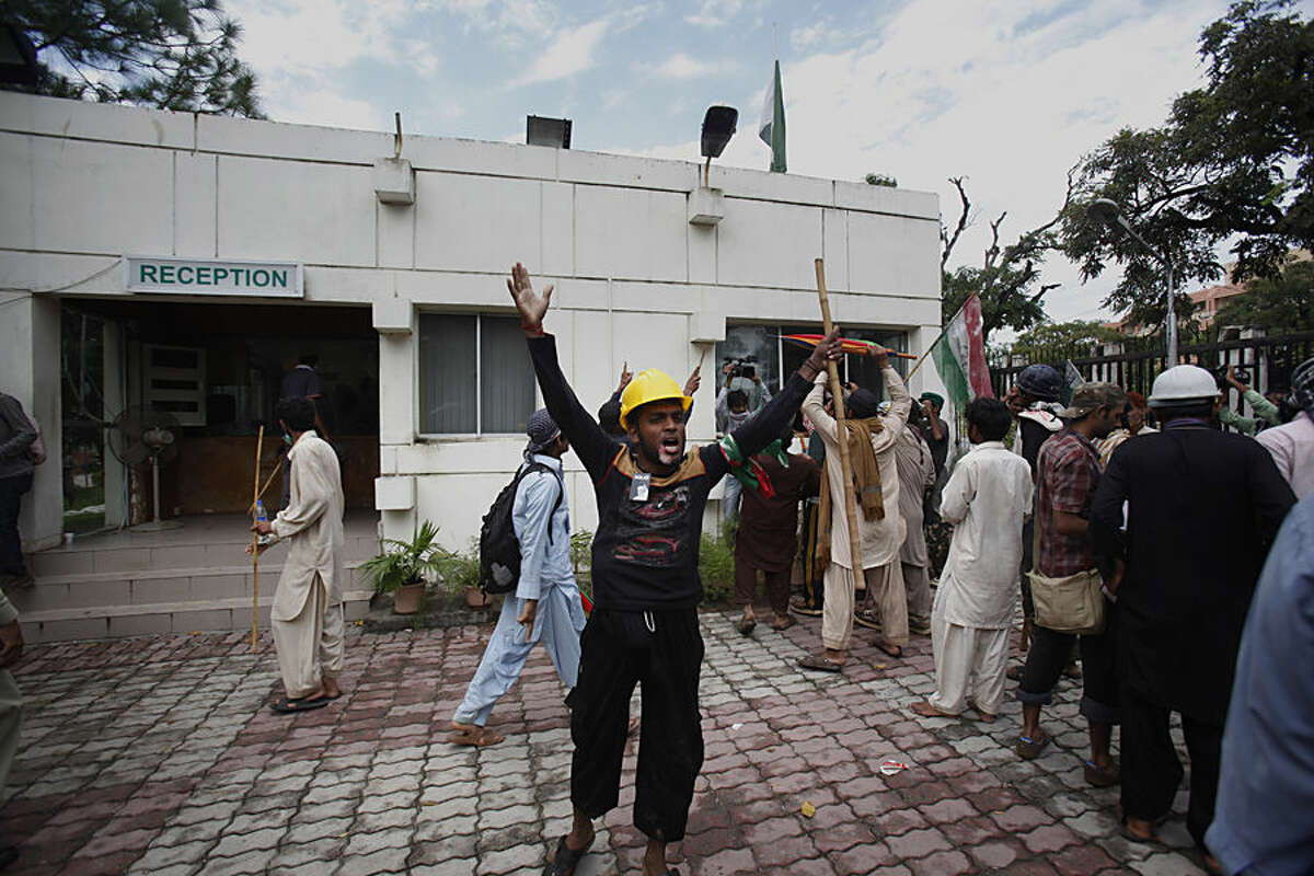 Pakistani protesters hold sticks and chant slogans after intruding into the state television building in Islamabad, Pakistan, Monday, Sept. 1, 2014. Anti-government protesters and Pakistani police have clashed once again as the demonstrators pushed into a sprawling government complex in the country's capital in an effort to try to reach the prime minister's official residence. (AP Photo/Anjum Naveed)