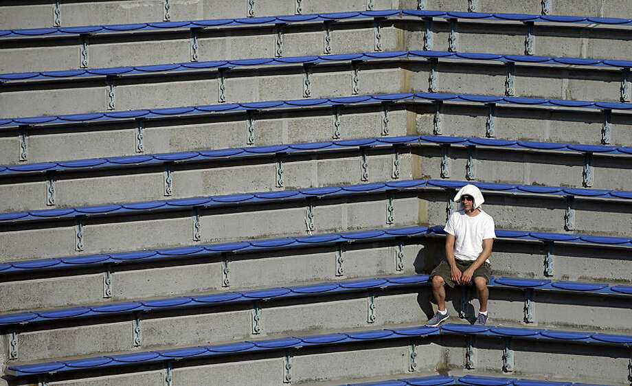 A tennis fan watches a doubles match on the Grandstand court during the third round of the 2014 U.S. Open tennis tournament Monday, Sept. 1, 2014, in New York. (AP Photo/Darron Cummings)