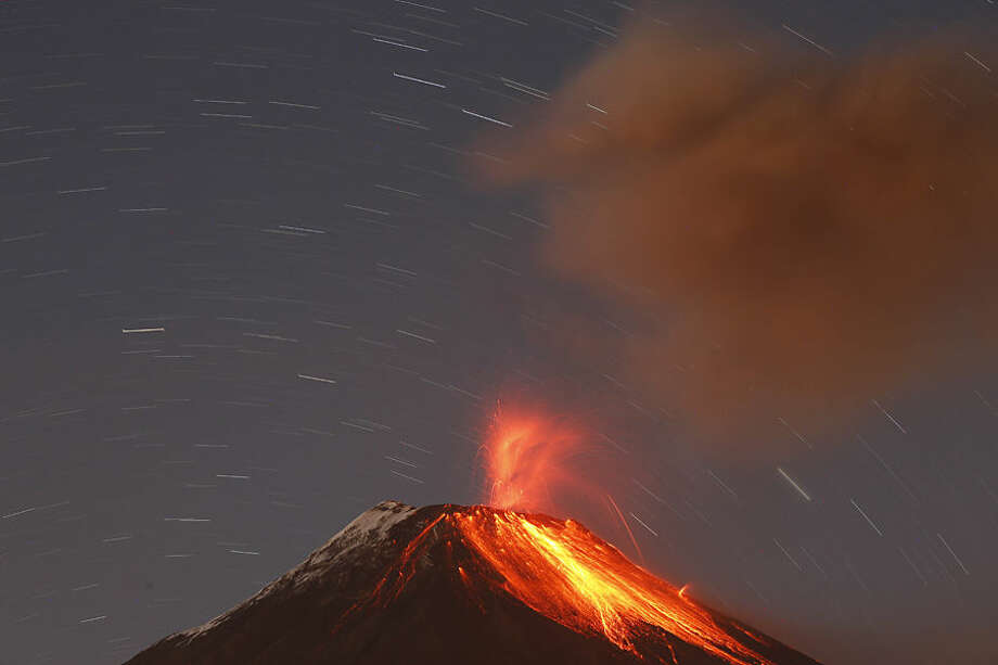 The Tungurahua volcano throws ash and stones during an eruption seen from Banos, Ecuador, Sunday, Aug. 31, 2014. The volcano entered an eruptive phase in 1999 and continues to this day. (AP Photo/Dolores Ochoa)
