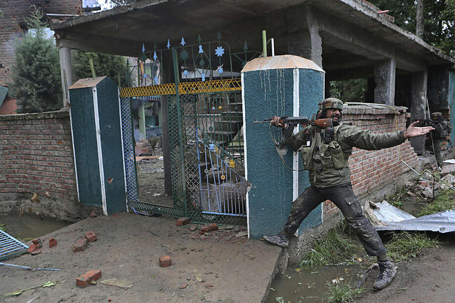 An Indian army solider shouts to his colleague to throw a magazine loaded with bullets during a gunbattle in Rajpora village south of Srinagar, India, Tuesday, Sept. 2, 2014. Indian government forces killed three suspected rebels in a gunbattle Tuesday in the disputed Himalayan region of Kashmir, where many residents oppose India's decades-long rule, officials said.(AP Photo/Dar Yasin)