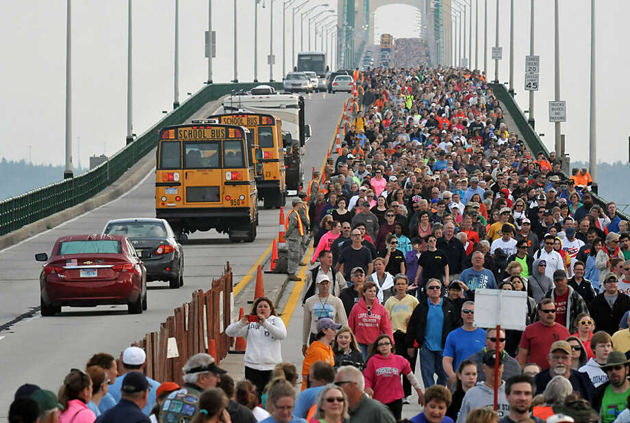 Walkers cross the five-mile-long Mackinac Bridge during the Labor Day walk, Monday, Sept. 1, 2014, during the 57th annual event in Mackinaw City, Mich. Lead by Michigan Gov. Rick Snyder, thousands cross from the upper peninsula of Michigan to the lower peninsula, the only day pedestrians are allowed on the span. (AP Photo/John L. Russell)