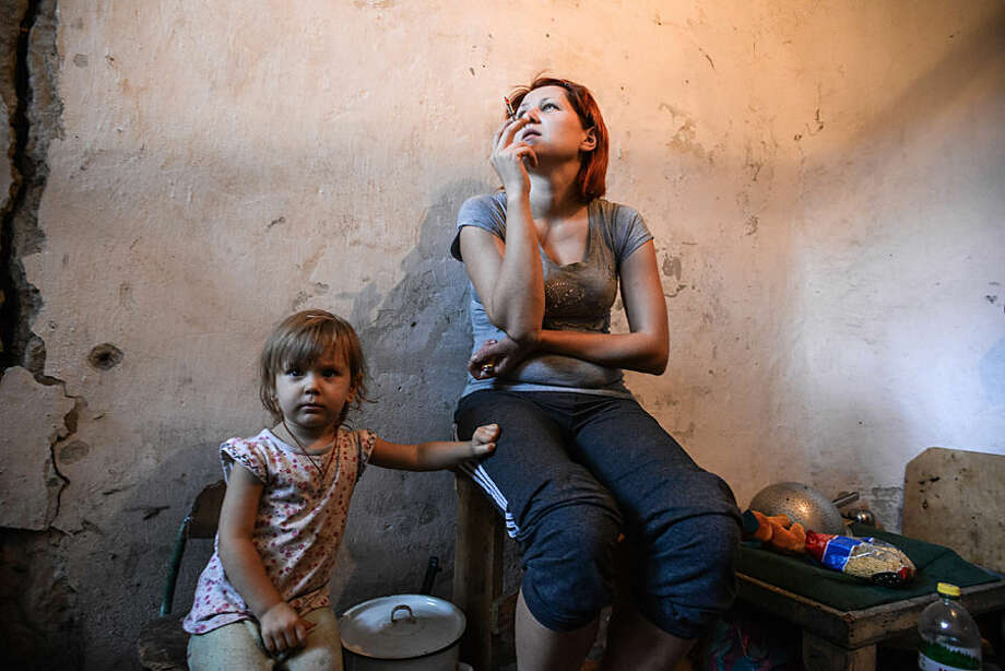 A mother and child hide in a bomb shelter in Petrovskiy district in Donetsk, eastern Ukraine, Monday, Sept. 1, 2014. The Petrovskiy district of Donetsk is currently a frontline and one of the districts which suffered the most from the artillery fights between Ukrainian army and Pro-Pussian rebels. (AP Photo/Mstislav Chernov)