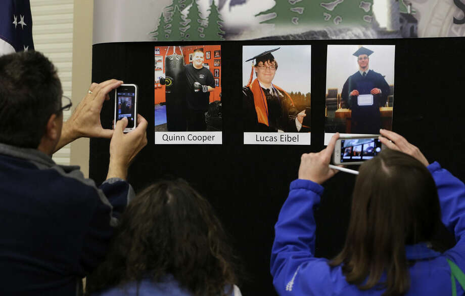 Reporters copy photographs of three of the victims of the mass shooting at Umpqua Community College that were displayed at a news conference, Friday, Oct. 2, 2015, in Roseburg, Ore. In the photos, from left, are Quinn Cooper, 18, Lucas Eibel,18, center, and Jason Johnson, 33. They were among those killed when Chris Harper Mercer walked into a class at the community college the day before and opened fire. (AP Photo/Rich Pedroncelli