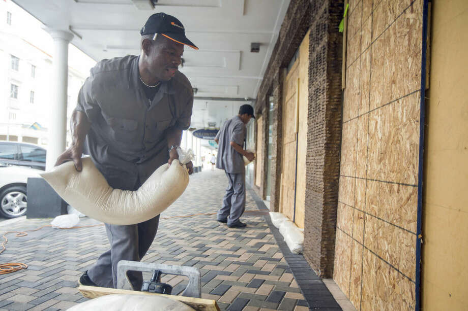 Perry Williams, 47, left, and Alaric Nixon, 28, place sandbags on the storefront of Diamond's International store, in preparation for the arrival of hurricane Joaquin in Nassau, Bahamas, Thursday, Oct. 1, 2015. Joaquin unleashed heavy flooding as it roared through sparsely populated islands in the eastern Bahamas as a Category 4 storm, with forecasters warning it could grow even stronger before carving a path that would take it near the U.S. East Coast. (AP Photo/Tim Aylen)