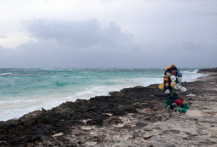 Hard hats hang from a post on the beach in north Eleuthera island, Bahamas, early Friday, Oct. 2, 2015. Hurricane Joaquin dumped torrential rains across the eastern and central Bahamas on Friday as a Category 4 storm. (AP Photo/Ben Fox)