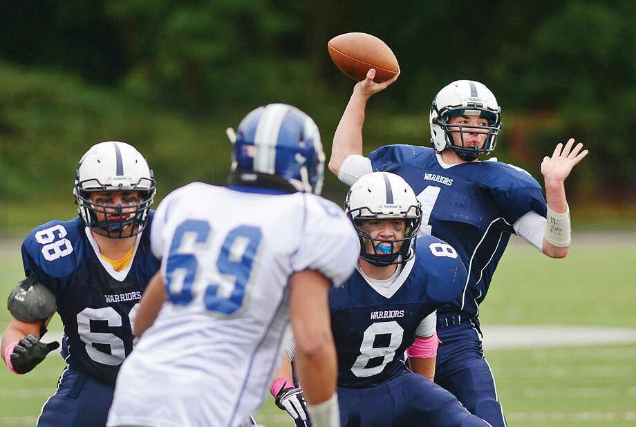Hour photo / Erik Trautmann Wilton High School football quarterback RJ Romeo readies to throw for a touchdown as the Warriors battle Fairfield Ludlowe in Wilton Saturday.