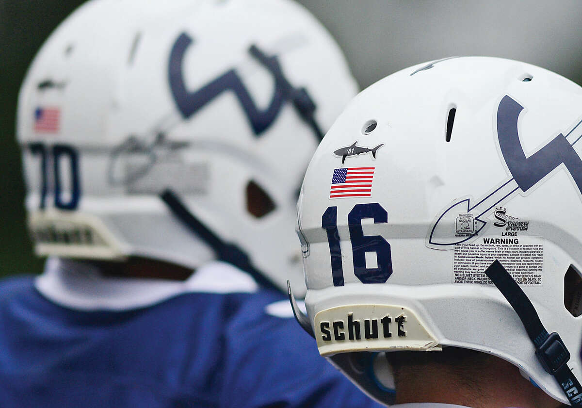 """Hour photo / Erik Trautmann Wilton High School football players honor former player Robbie """"The Shark"""" Keers with a decal noting his jersey number, #81, as the Warriors played Fairfield Ludlowe in Wilton Saturday."""