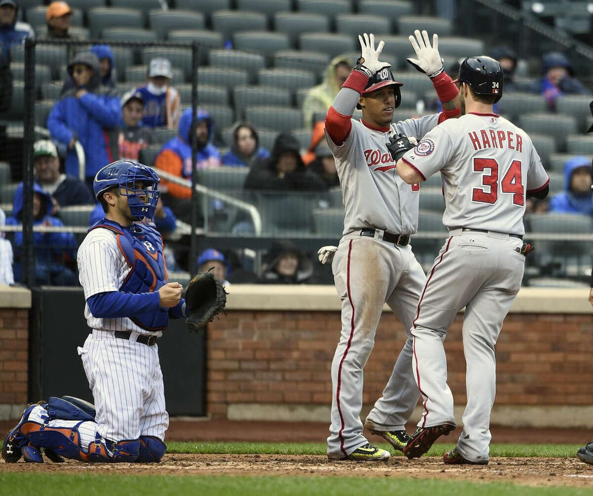 New York Mets catcher Travis d'Arnaud watches Washington Nationals' Yunel Escobar (5) and Bryce Harper (34) celebrate Harper's two-run home run that scored Escobar in the eighth inning of the first baseball game of a doubleheader, Saturday, Oct. 3, 2015, in New York. The Nationals won 3-1. (AP Photo/Kathy Kmonicek)