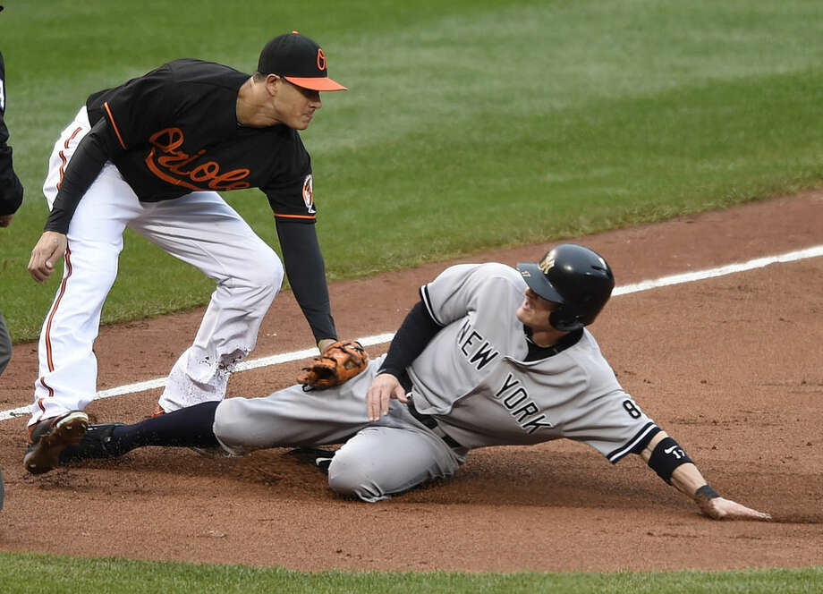 Baltimore Orioles third baseman Manny Machado tags out New York Yankees' Brendan Ryan at third as he tried to advanced on a single by Brett Gardner in the third inning of the first baseball game of a doubleheader in Baltimore, Saturday, Oct. 3, 2015. (AP Photo/Gail Burton)
