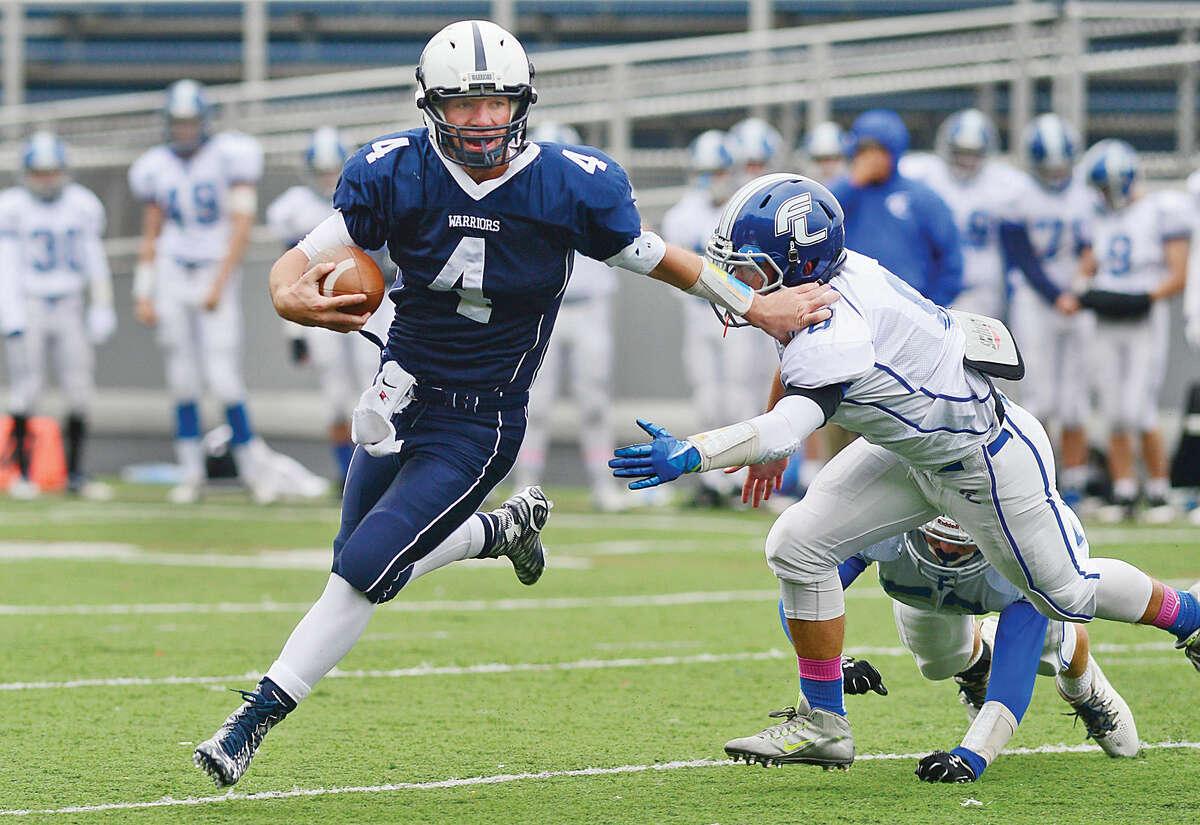 Hour photo / Erik Trautmann Wilton High School football quarterback RJ Romeo looks for rushing yardage as the Warriors battle Fairfield Ludlowe in Wilton Saturday.