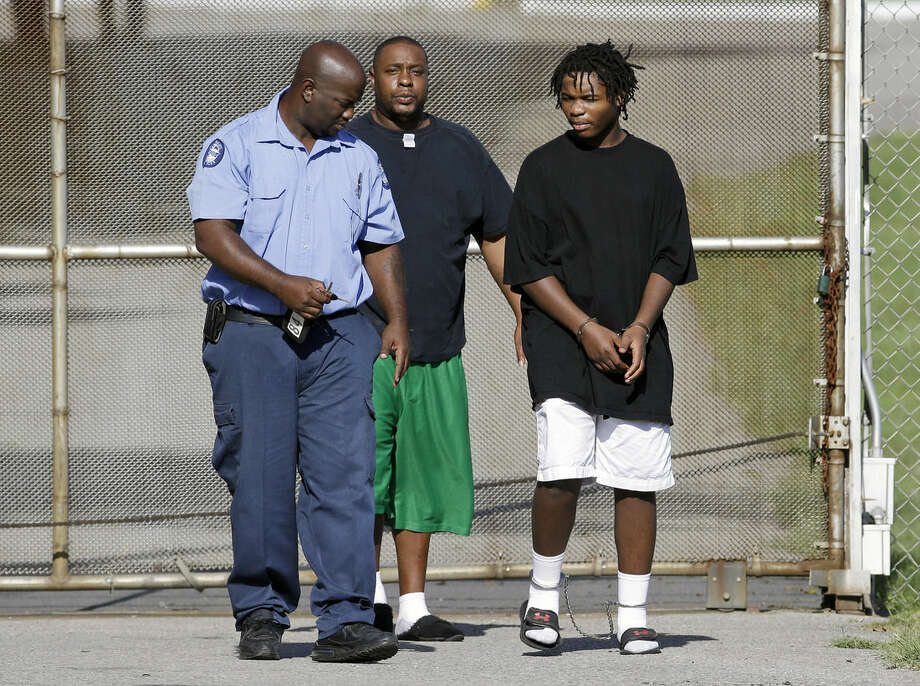 One of 32 escaped teenagers, right, is taken into custody after he was turned in by family members, according to a Tennessee Department of Children's Services spokesman, in front of the Woodland Hills Youth Development Center Tuesday, Sept. 2, 2014, in Nashville, Tenn. The teenagers, ages 14 to 19, escaped from the facility Monday night. (AP Photo/Mark Humphrey)