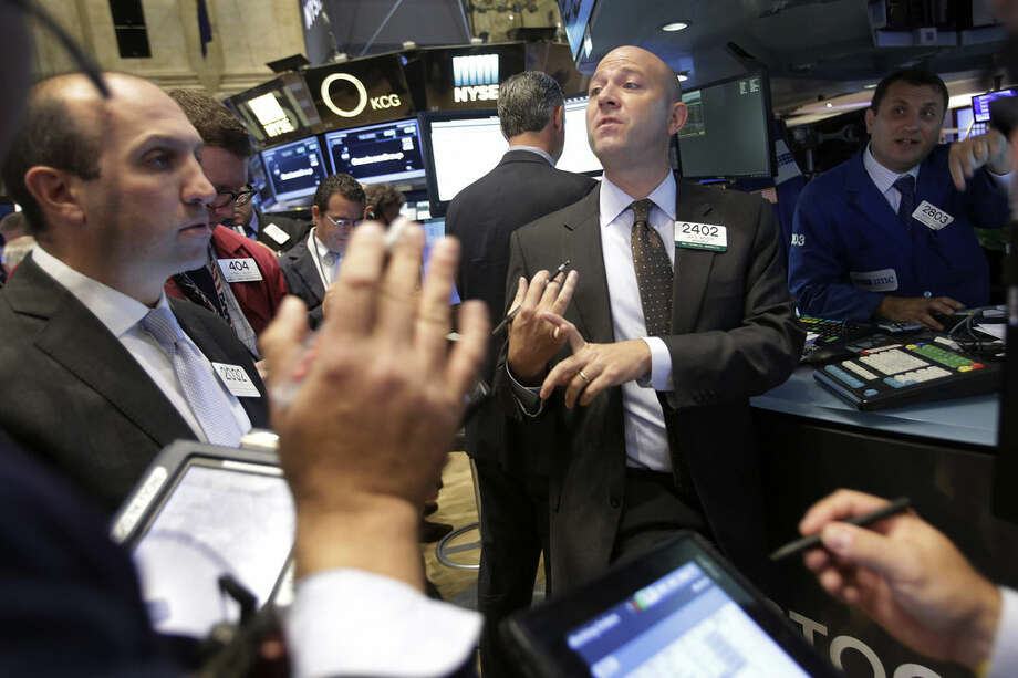 Jay Woods, with Goldman Sachs, center, works with other stock traders at the New York Stock Exchange, Monday, Oct. 5, 2015 in New York. World stocks rose Monday after weak U.S. jobs data prompted expectations the Federal Reserve might postpone an interest rate hike. (AP Photo/Mark Lennihan)
