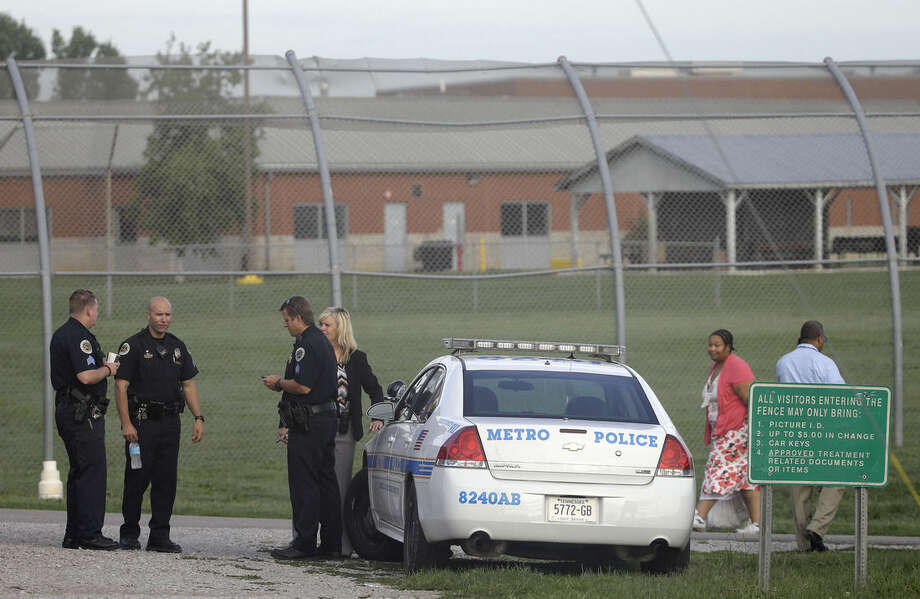 Police work in front of the Woodland Hills Youth Development Center Tuesday, Sept. 2, 2014, in Nashville, Tenn. Thirty-two teens escaped from a Nashville youth detention center by crawling through a weak spot in a fence late Monday, and more than half of them were still on the run Tuesday, a spokesman said. (AP Photo/Mark Humphrey)