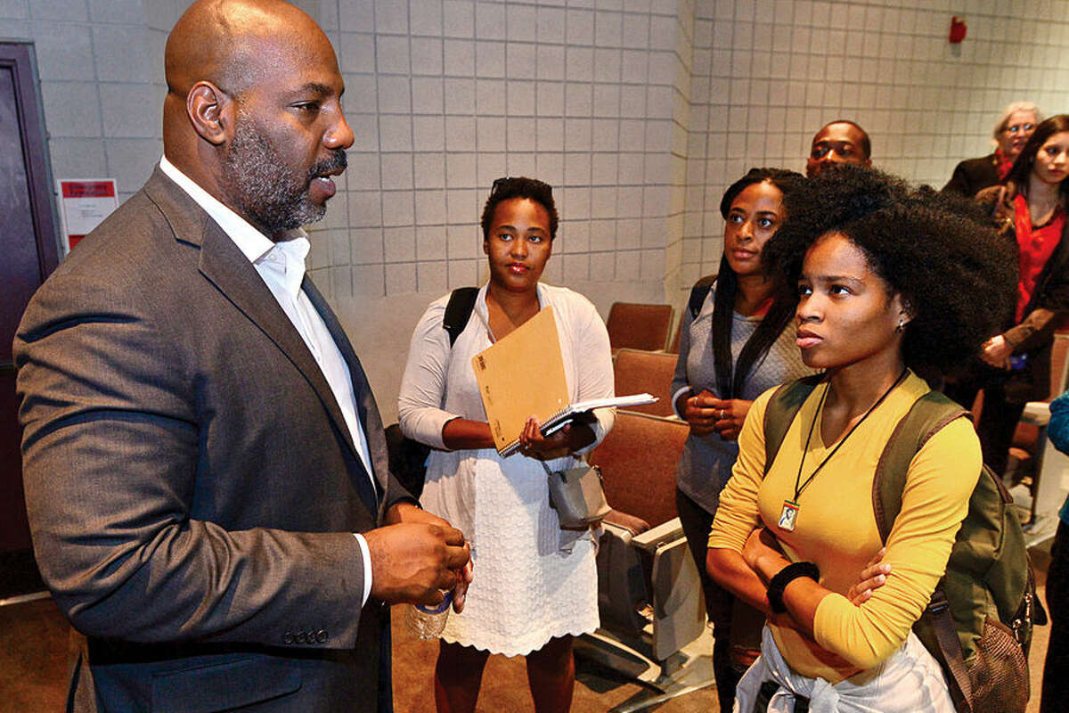 Hour photo / Erik Trautmann Norwalk Community Collegestudents including Toni Livingston, right, chat with staff writer for the New Yorker magazine and Associate Professor of History and Director of the Institute for African American Studies at University of Connecticut in Storrs, William Jelani Cobb, left, after Cobb spoke at NCC Tuesday afternoon.