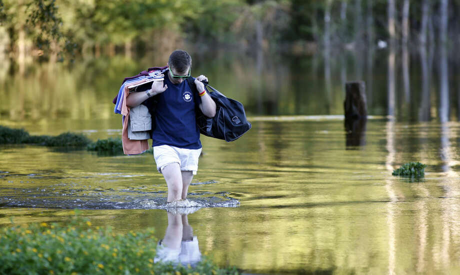 Sean Nance walks through floodwaters carrying some work clothes as he evacuates from his apartment in the Ashborough subdivision near Summerville, S.C., Tuesday, Oct. 6, 2015. Residents are concerned that the Ashley River will continue to rise as floodwaters come down from Columbia. (AP Photo/Mic Smith)