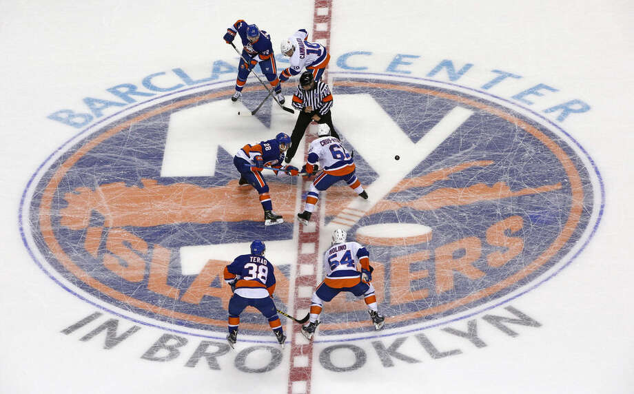 FILE - In this July 8, 2015, file photo, New York Islanders forward Miks Indrasis (28) and Victor Crus-Rydberg (61) face off during the New York Islanders' Blue and White scrimmage at Barclays Center, the team's new home, in New York. The Islanders are entering their first season at the Barclays Center, home to the NBA's Brooklyn Nets since 2012, after spending their first 43 years at the Nassau Coliseum in Uniondale, N.Y. The team's headquarters and practice facility remain on Long Island, where the players continue to live. (AP Photo/Kathy Willens, File)