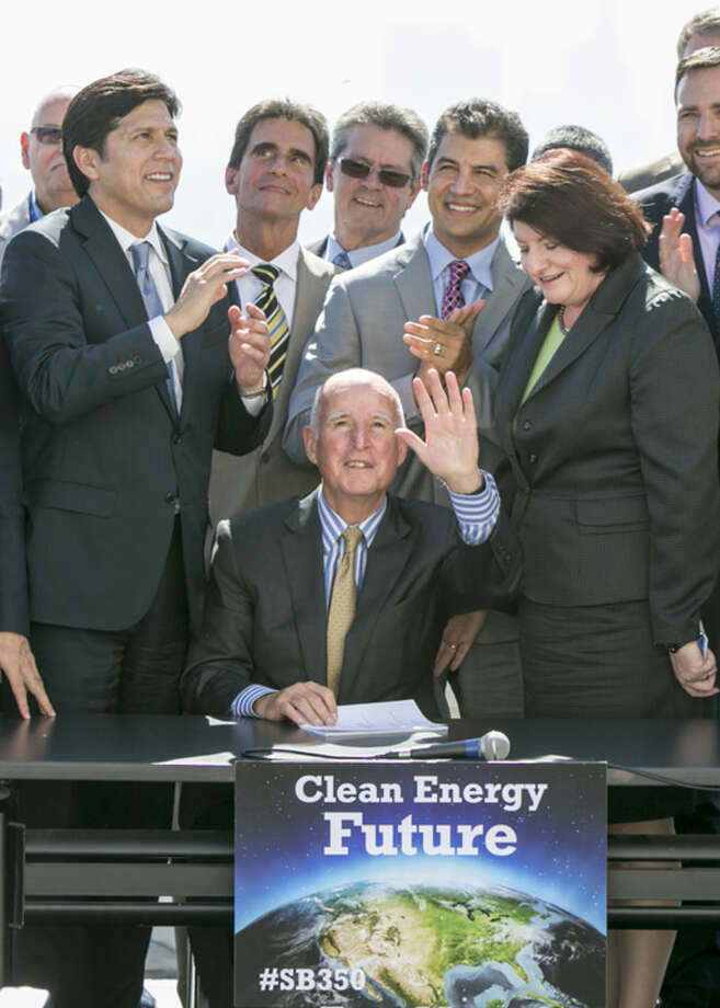 California Gov. Jerry Brown, sitting center, waves after signing bill SB350 by Senate President pro Tempore Kevin De Leon, left, to combat climate change by increasing the state's renewable electricity use to 50 percent and doubling energy efficiency in existing buildings by 2030 at a ceremony at the Griffith Observatory in Los Angeles on Wednesday, Oct. 7, 2015. Assembly speaker Toni Atkins, far right. (AP Photo/Damian Dovarganes)