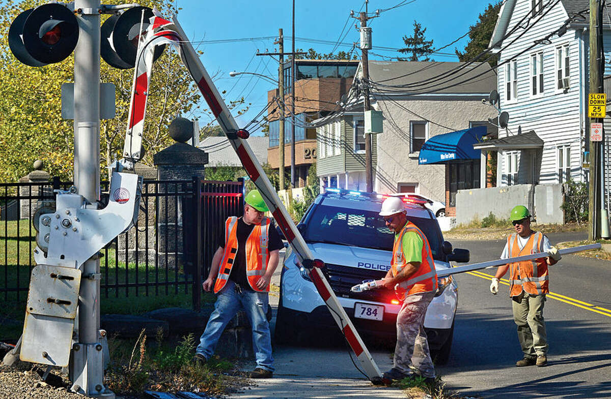 Hour photo / Erik Trautmann The Metro North Railroad workers perpare to replace a crossing barrier at Broad St after it was struck and damaged by a motor vehicle Wednesday.