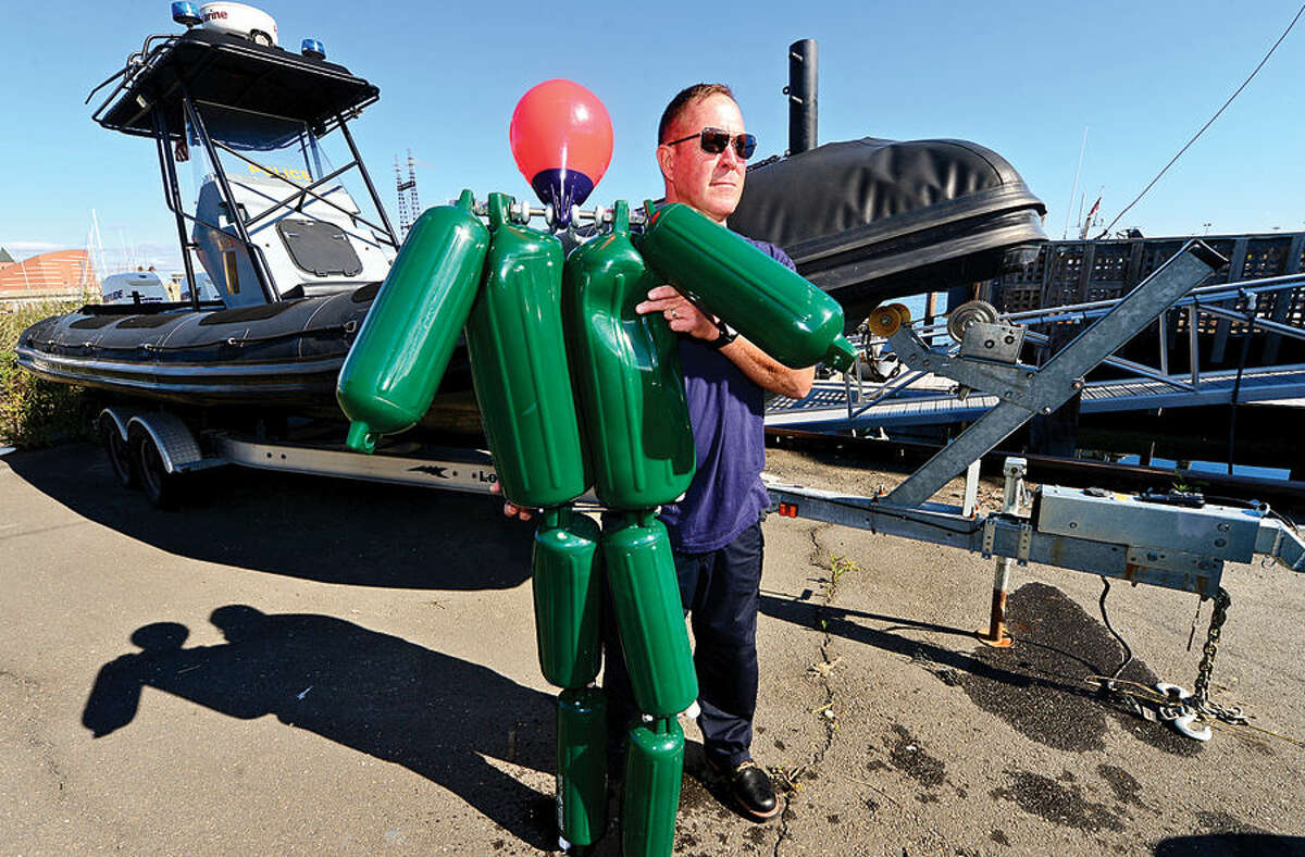 Hour photo / Erik Trautmann Norwalk Marine Police Seargent Peter Lapak poses with their new training aide,