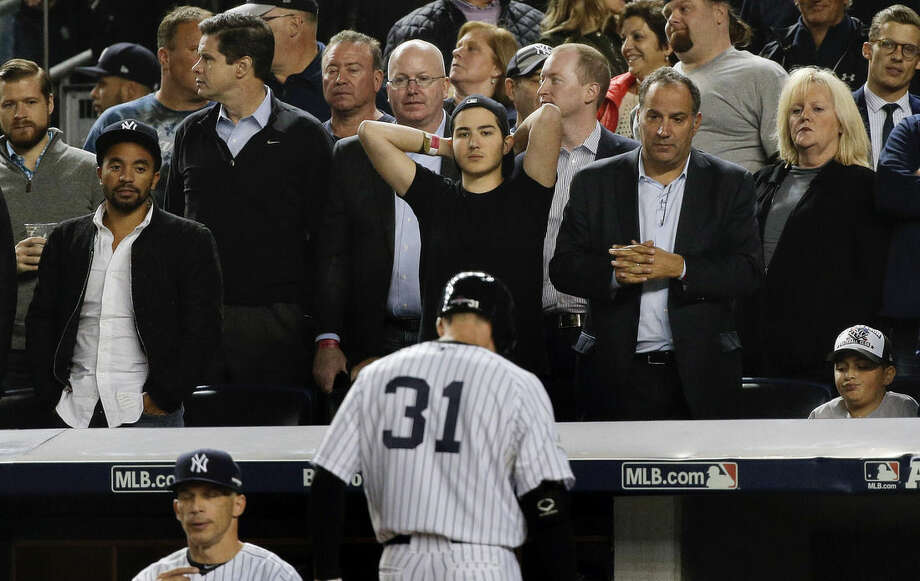 Baseball fans watch as New York Yankees' Greg Bird (31) walks back to the dugout after being called out on strikes with a man on base during the seventh inning of the American League wild card baseball game against the Houston Astros, Tuesday, Oct. 6, 2015, in New York. The Astros won 3-0. (AP Photo/Julie Jacobson)