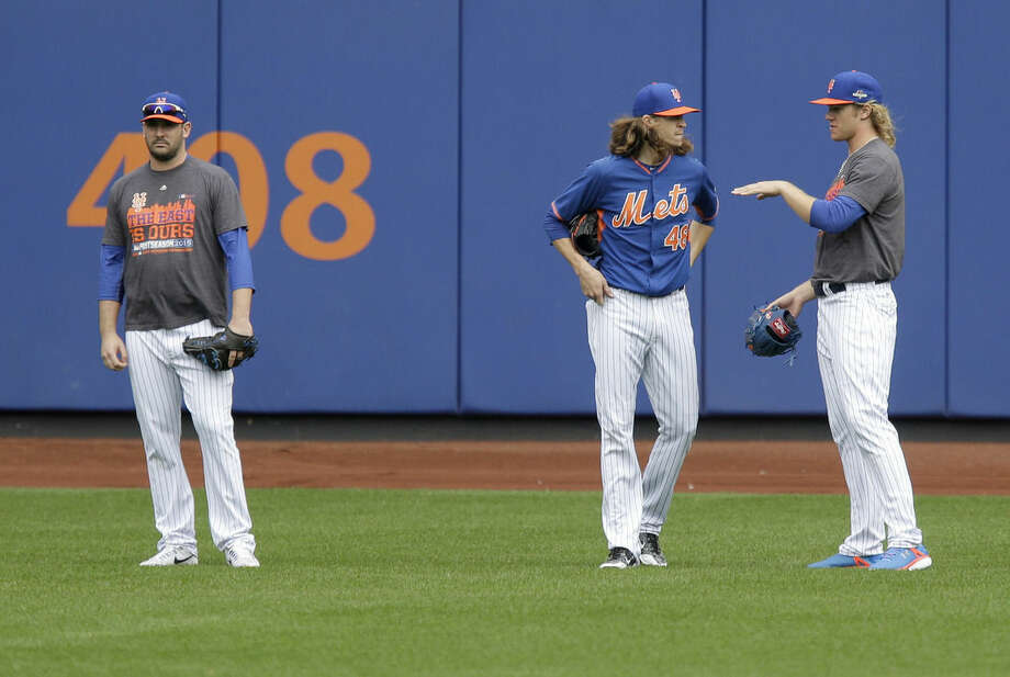 New York Mets pitchers Matt Harvey, left, Jacob deGrom, center, and Noah Syndergaard stand in the outfield during a workout at Citi Field, Wednesday, Oct. 7, 2015 in New York. The Mets will play the Los Angeles Dodgers in a National League Division Series starting Friday in Los Angeles.(AP Photo/Seth Wenig)