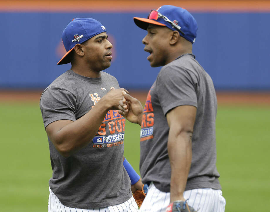 New York Mets' Yoenis Cespedes, left, and Curtis Granderson fist bump during a workout at Citi Field, Wednesday, Oct. 7, 2015 in New York. The Mets will play the Los Angeles Dodgers in a National League Division Series starting Friday in Los Angeles. (AP Photo/Seth Wenig)