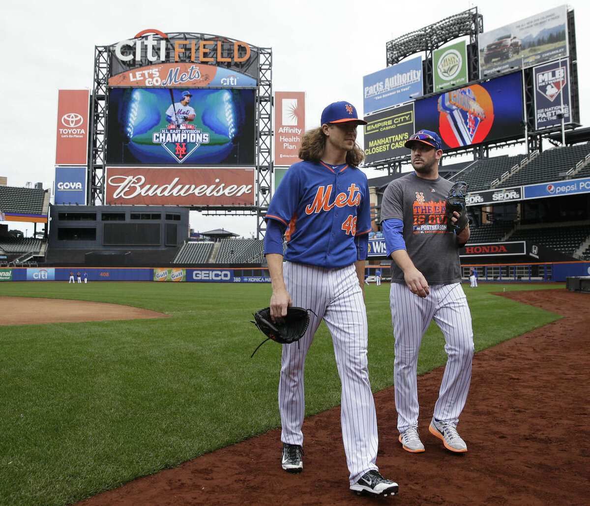New York Mets pitchers Jacob deGrom, left, and Matt Harvey leave the field during a workout at Citi Field, Wednesday, Oct. 7, 2015 in New York. The Mets will play the Los Angeles Dodgers in a National League Division Series starting Friday in Los Angeles. (AP Photo/Seth Wenig)