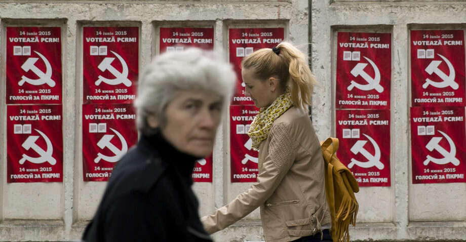 In this Thursday, May 28, 2015 photo, pedestrians walk past election posters for the Communist Party in Chisinau, the capital city of Moldova. Repeated attempts to sell radioactive materials signal that a thriving nuclear black market has emerged in this impoverished corner of Eastern Europe on the fringes of the former Soviet Union. (AP Photo/Vadim Ghirda)