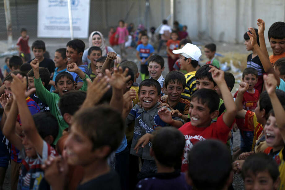 Children laugh as they play inside a camp for internally displaced persons in Irbil, 350 kilometers (220 miles) north of Baghdad, Iraq, Saturday, August 30, 2014. An estimated 1.5 million people have been displaced by fighting in Iraq since the Islamic State's rapid advance began in June. (AP Photo/Marko Drobnjakovic)