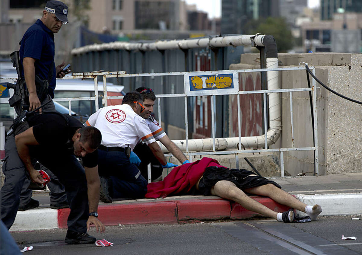 Israeli medics tend to wounded Palestinian man after he stabbed a few Israelis in an attack in Tel Aviv, Israel, Thursday, Oct. 7, 2015. Israeli police says a soldier shot and killed an Arab attacker after he stabbed four people with a screwdriver in Tel Aviv. (AP Photo/Oded Balilty)