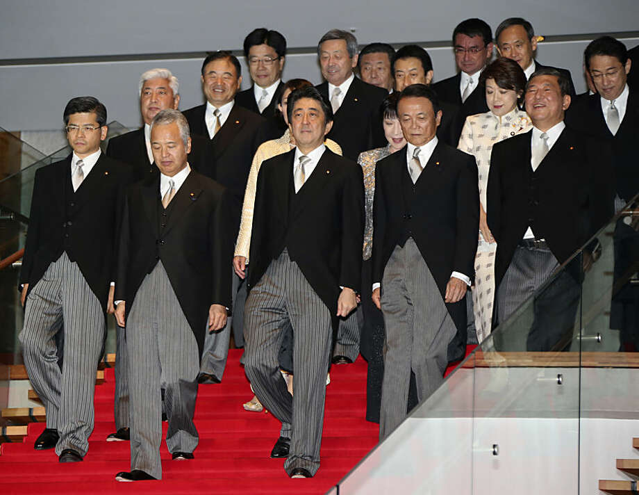 Japanese Prime Minister Shinzo Abe, center, leads his new cabinet, for a group photo session at the prime minister's official residence in Tokyo,Wednesday, Oct. 7, 2015. Prime Minister Abe has reshuffled his Cabinet to focus on reviving the world's No. 3 economy.(AP Photo/Koji Sasahara)