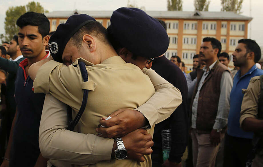 Indian police officers embrace each other as they cry during the wreath laying ceremony of their colleague officer Altaf Ahmed in Srinagar, Indian controlled Kashmir, Wednesday, Oct. 7, 2015. Suspected militants gunned down Ahmed in a brief shootout at Gund Dachin area of Bandipora in north Kashmir on Wednesday. (AP Photo/Mukhtar Khan)