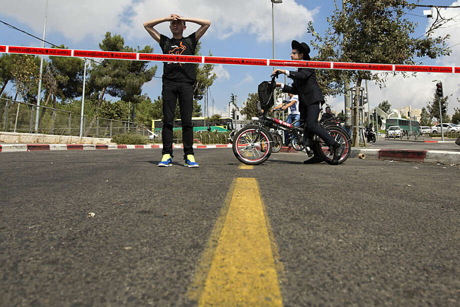 Israelis look at the scene of a stabbing attack in Jerusalem, Thursday, Oct. 8, 2015. A Palestinian stabbed a Jewish seminary student in Jerusalem on Thursday as the Israeli prime minister barred all Cabinet ministers and lawmakers from visiting a sensitive holy site in the Old City in an effort to calm tensions that have gripped the country for weeks. (AP Photo/Sebastian Scheiner)