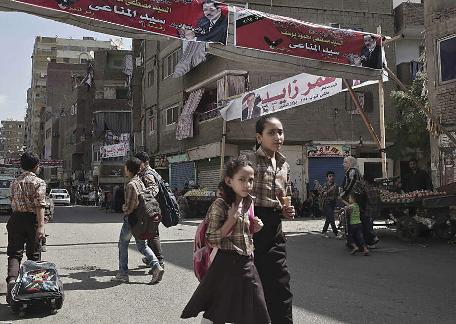 """Egyptian school children make their way home after school in front of a banner with the photo of a parliamentary candidate,top center, and Arabic that reads, """"running for the youth, together on the right path, Sayed Al-Minaay,"""" on a street in Boulaq El Dakrour district of Giza, near Cairo, Egypt, Thursday, Oct. 8, 2015. Egypt's long-awaited parliamentary elections will start on Oct. 18-19, a hoped-for step toward democracy amid a harsh crackdown on dissent. The second stage of the staggered vote will take place on Nov. 22-23. Final results will be announced in early December. (AP Photo/Nariman El-Mofty)"""