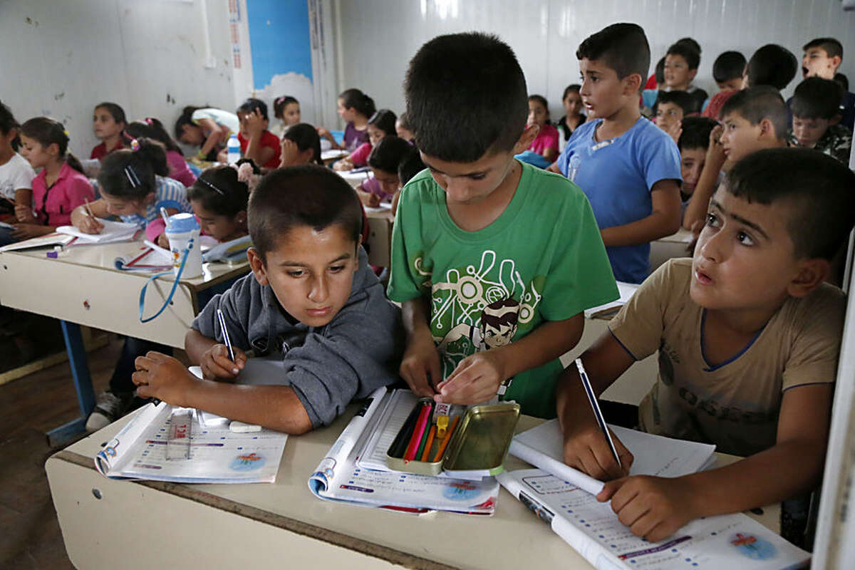 In this Wednesday, Oct. 7, 2015 photo, third grade students are given lessons at a makeshift school in a Syrian Refugee camp in Irbil, northern Iraq. As many teachers have migrated from Iraq to Europe, schools are facing a severe shortage so that often more than 45 Students have to study in each class. (AP Photo/Seivan M. Salim)