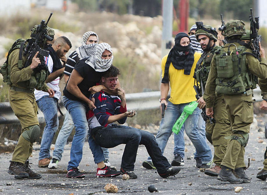 Undercover Israeli police officers and Israeli soldiers detain a wounded Palestinian demonstrator, being pulled up, during clashes near Ramallah, West Bank, Wednesday, Oct. 7, 2015. Palestinian attackers stabbed Israelis in Jerusalem and southern Israel while Israeli troops clashed with Palestinian protesters in the West Bank on Wednesday as Israel's president sought to calm tensions, insisting there will be no changes at a contested Jerusalem holy site that is at the heart of the latest escalation. (AP Photo/Majdi Mohammed)